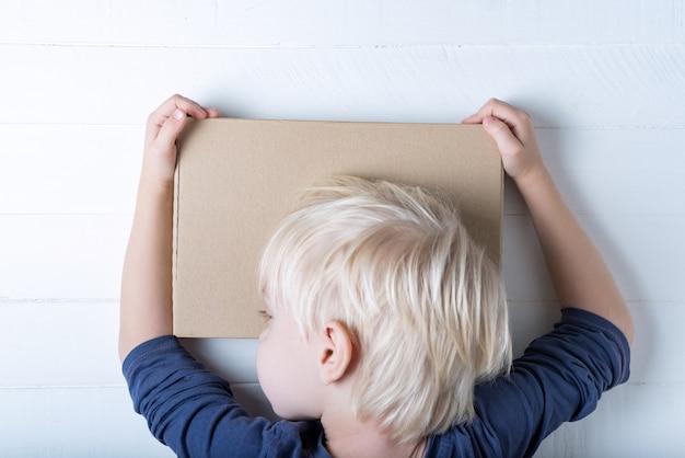Rapaz, abraçando um pacote. bonita criança segurando uma caixa. , vista do topo