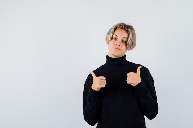 Rapaz adolescente aparecendo com o polegar duplo no suéter preto e olhando melancólico, vista frontal.