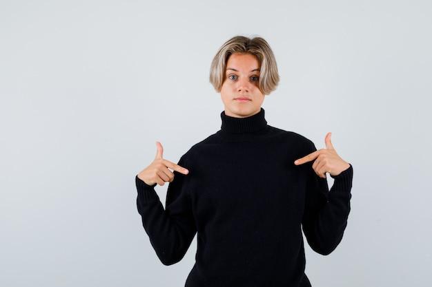 Rapaz adolescente apontando para baixo com um suéter preto e olhando melancólico, vista frontal.