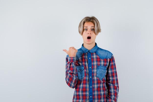 Rapaz adolescente apontando para o lado esquerdo com o polegar em uma camisa quadriculada e olhando perplexo, vista frontal.