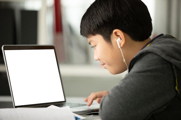 Rapaz adolescente asiático usando computador portátil em casa,
