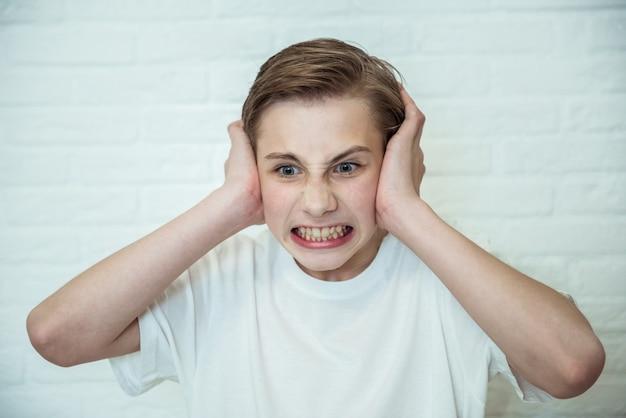 Rapaz adolescente chateado, fechando as orelhas. retrato de cara bravo, cansado de escândalos ou fofocas. conceito de emoção negativa