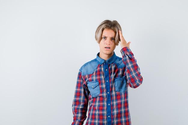 Rapaz adolescente com a mão na cabeça em camisa quadriculada e olhando sério, vista frontal.