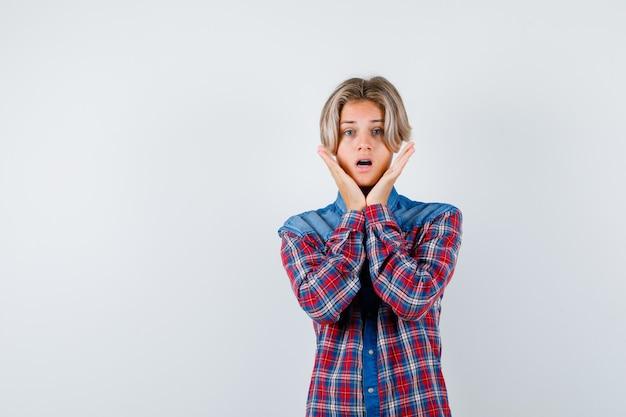 Rapaz adolescente com as mãos perto das bochechas em camisa quadriculada e parecendo perplexo. vista frontal.