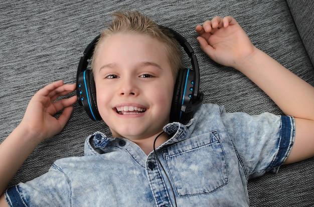 Rapaz adolescente com auscultadores a ouvir música no sofá em casa rapaz feliz e sorridente a descansar no sofá em casa
