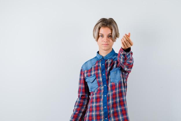 Rapaz adolescente com camisa quadriculada, mostrando o gesto de dinheiro e olhando confiante, vista frontal.