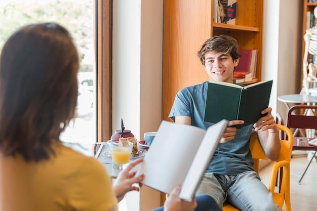 Rapaz adolescente com livro a olhar para a namorada