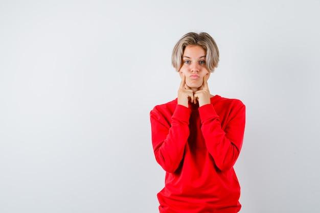 Rapaz adolescente com suéter vermelho, mantendo os dedos nas bochechas, fazendo beicinho nos lábios e parecendo cômico, vista frontal.