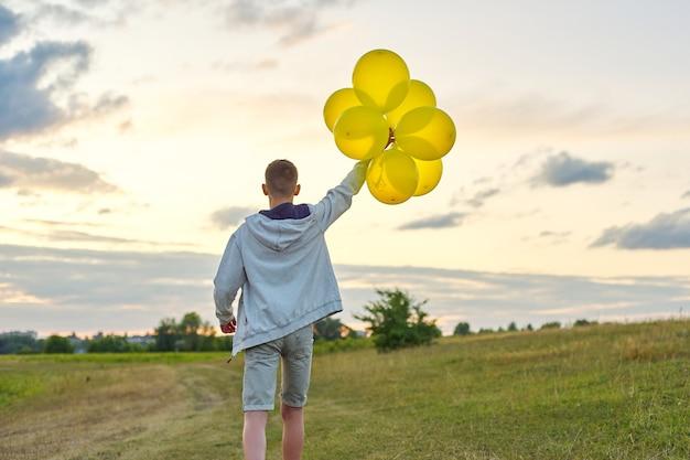 Rapaz adolescente correndo com balões, vista traseira. natureza, prado, céu em fundo de nuvens. férias, aniversário, conceito de liberdade de estilo de vida