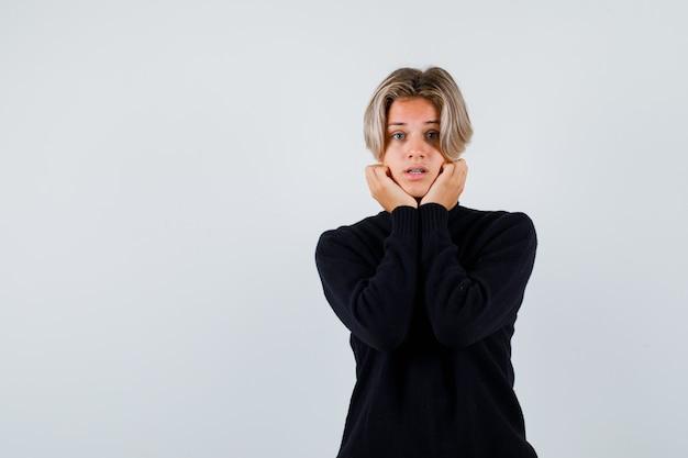 Rapaz adolescente de suéter preto, apoiando o queixo nas mãos e olhando surpreso, vista frontal.