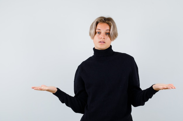 Rapaz adolescente de suéter preto, espalhando as palmas das mãos e olhando pensativo, vista frontal.