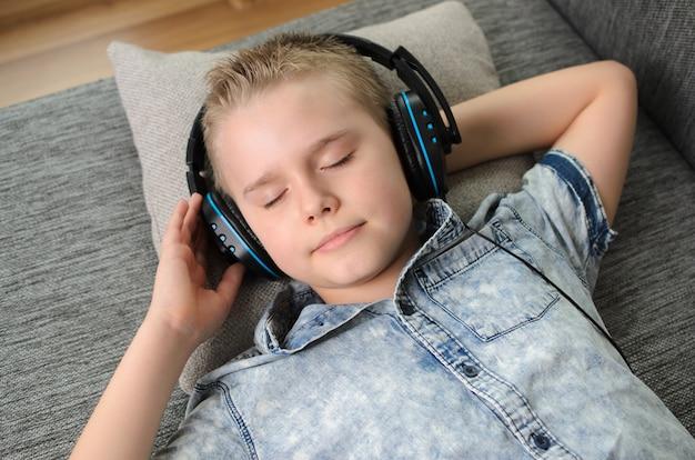 Rapaz adolescente em fones de ouvido ouve música no sofá em casa. adolescente gosta de música - retrato de um menino loiro enquanto estava deitado no sofá dentro de casa. hora de relaxar.