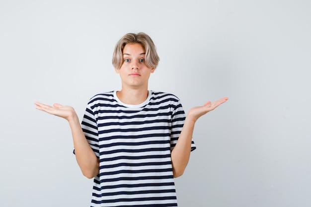 Rapaz adolescente em t-shirt, encolhendo os ombros e parecendo indeciso, vista frontal.