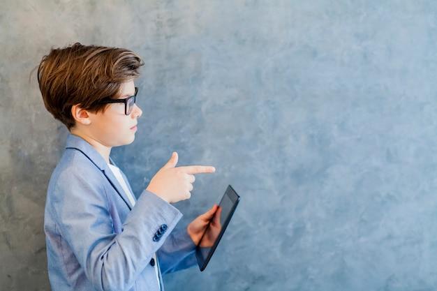 Rapaz adolescente escolar em óculos detém tablet pc