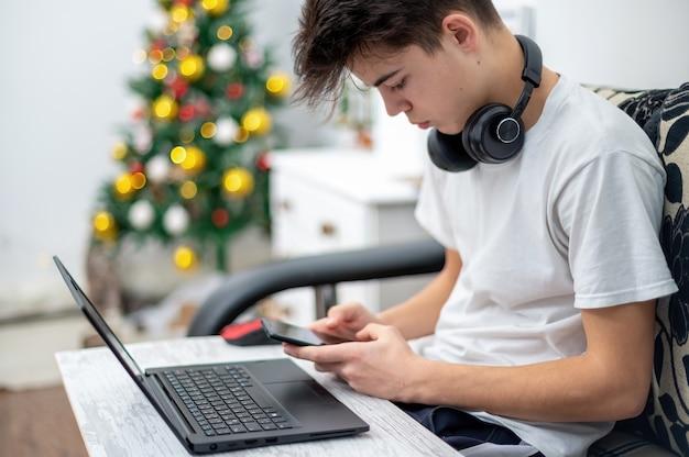 Rapaz adolescente está usando smartphone com fones de ouvido, laptop de joelhos em casa. árvore de natal na parede. rosto sério e focado
