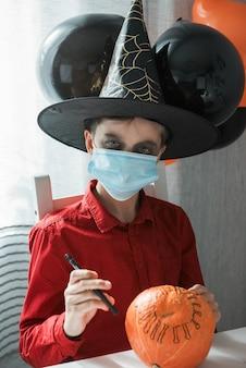 Rapaz adolescente fantasiado, preparando-se para a celebração do halloween, desenhando uma abóbora. carnaval de halloween com nova realidade com conceito de pandemia