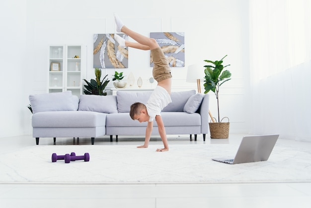 Rapaz adolescente fazendo as mãos em pé exercícios na acolhedora sala de estar.