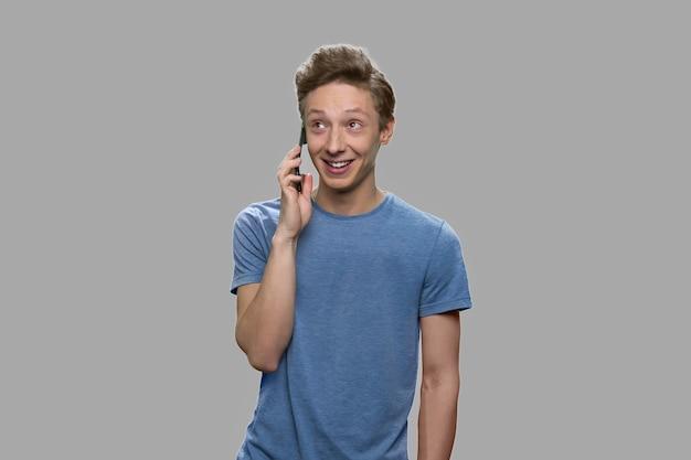 Rapaz adolescente feliz falando no celular. adolescente alegre usando telefone celular contra um fundo cinza.