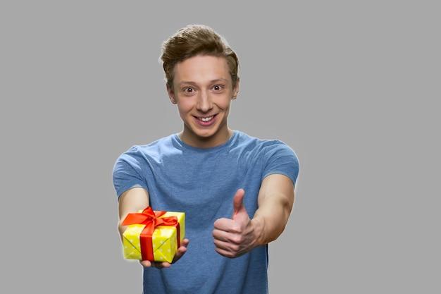 Rapaz adolescente mostrando a caixa de presente e o polegar para cima. cara caucasiano bonito dando caixa de presente. conceito de férias felizes.