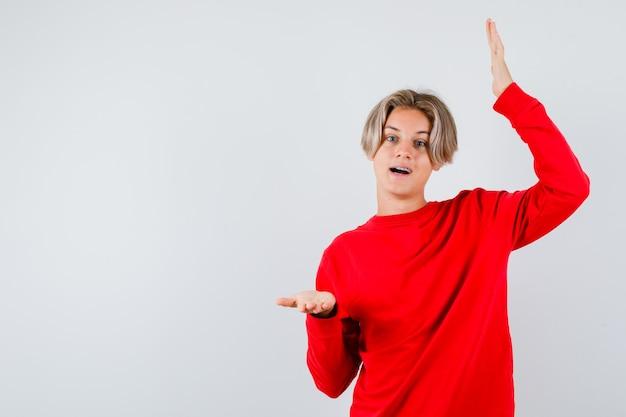 Rapaz adolescente mostrando sinal de tamanho grande, abrindo a boca no suéter vermelho e parecendo pasmo, vista frontal.