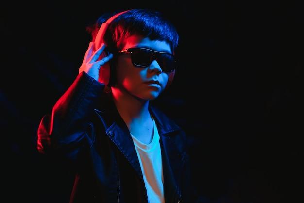 Rapaz adolescente ouvindo música com fones de ouvido, retrato de tendências de luz de néon. olha para a câmera
