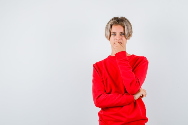 Rapaz adolescente roendo a unha no suéter vermelho e parecendo inquieto, vista frontal.
