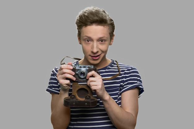 Rapaz adolescente segurando uma câmera vintage em fundo cinza. jovem fotógrafo caucasiano olhando para a câmera. conceito de pessoas, hobby e tecnologia.