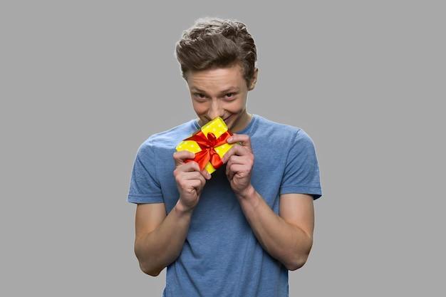 Rapaz adolescente tímido segurando uma pequena caixa de presente. adolescente bonito com pé de caixa de presente em fundo cinza.
