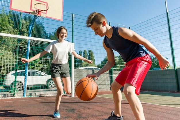 Rapaz adolescente treinando sua namorada jogando basquete, jogo de basquete de rua