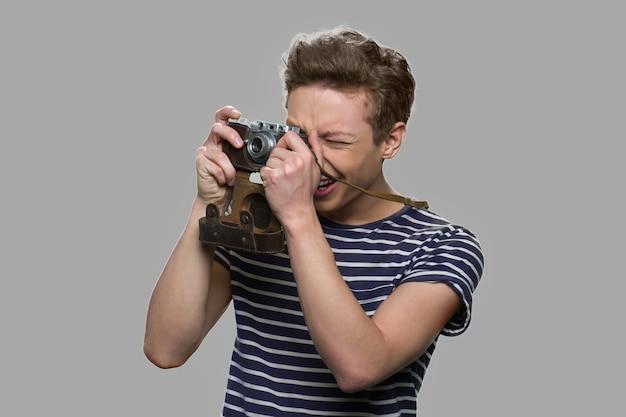 Rapaz adolescente usando a velha câmera retro. rapaz adolescente fotografando usando uma câmera vintage. conceito de hobby.
