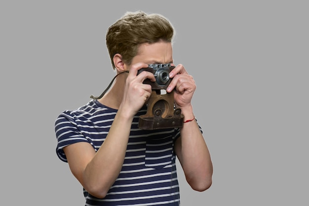Rapaz adolescente usando câmera vintage. cara jovem tirando foto com a câmera retro contra um fundo cinza. conceito de pessoas, tecnologia e hobby.