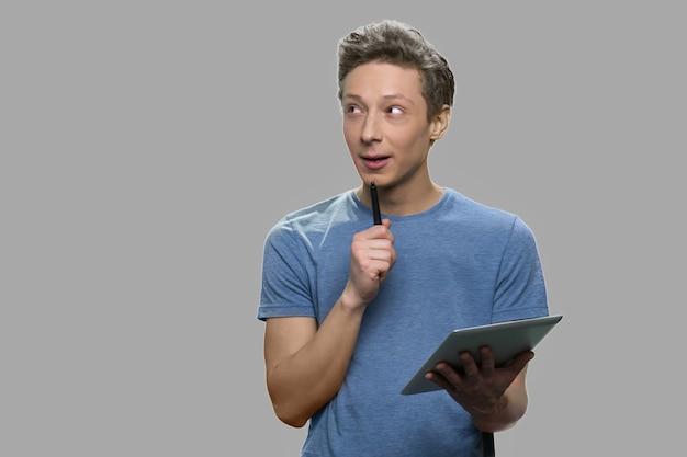 Rapaz adolescente usando o tablet pc com expressão pensativa. cara inteligente e pensativo trabalhando em tablet digital contra um fundo cinza.