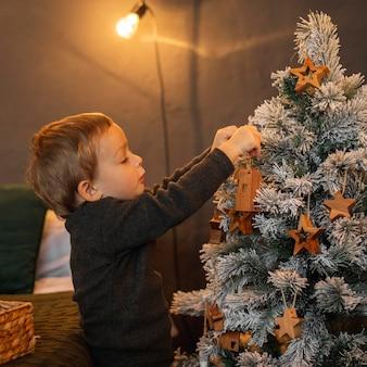 Rapaz adorável a decorar a árvore de natal