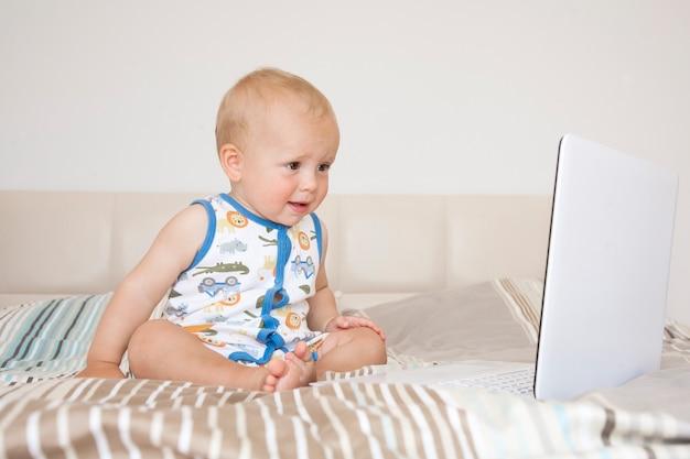 Rapaz adorável criança loira sentado na cama e olhando para o laptop em casa, dentro de casa. criança com computador tablet.