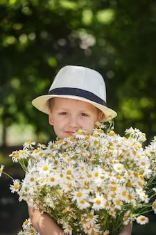 Rapaz adorável retrato em um chapéu com grande buquê branco de camomiles