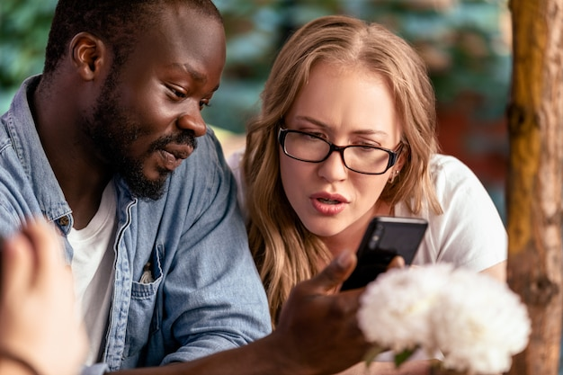 Rapaz africano está mostrando smartphone chocante no smartphone para linda mulher caucasiana