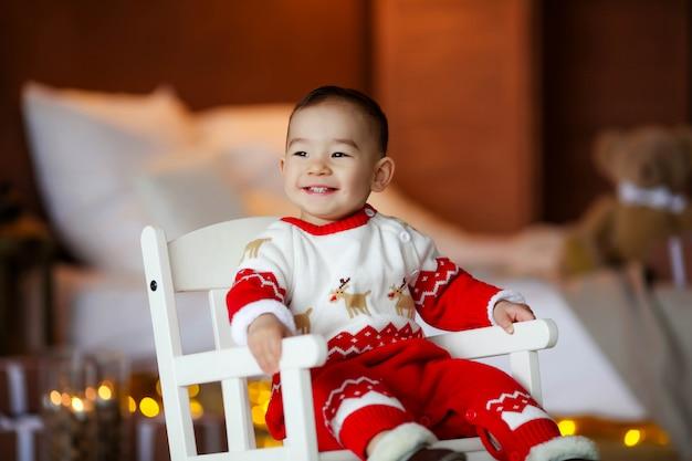 Rapaz alegre, 2-3 anos de aparência asiática em um quarto em casa, em um terno vermelho de natal