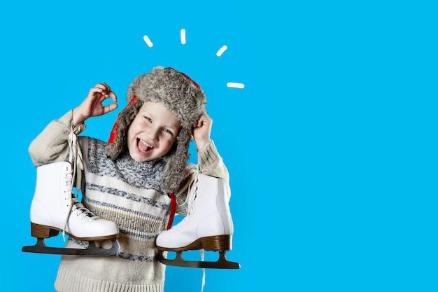 Rapaz alegre com um chapéu com gorro segurando patins de gelo no fundo azul