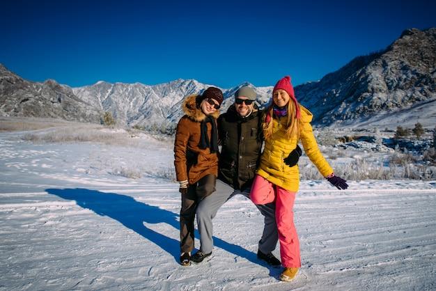 Rapaz alegre e duas garotas bonitas posando com roupas de inverno coloridas