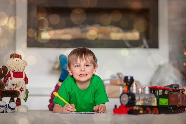 Rapaz alegre é uma carta para o papai noel, perto da árvore de natal. infância feliz, tempo para realizar desejos.