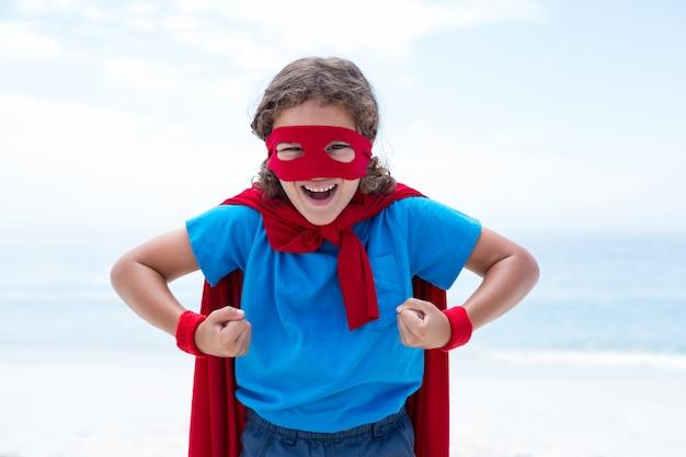 Rapaz alegre em traje de super-heróis, flexionando os músculos na beira-mar