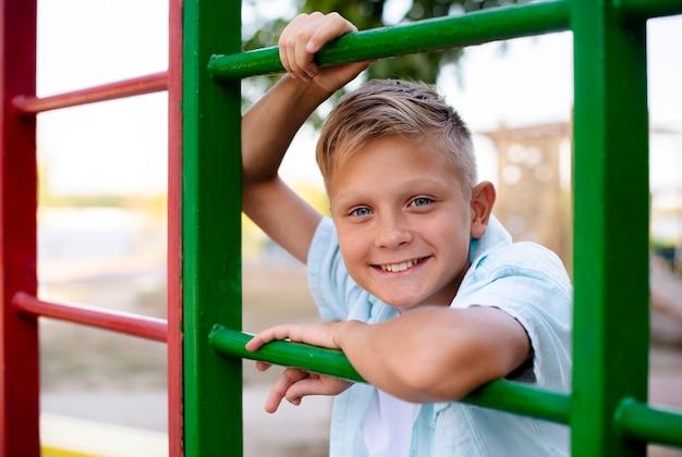 Rapaz alegre, jogando sozinho no parque infantil
