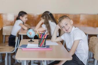 Rapaz alegre, olhando para a câmera na sala de aula