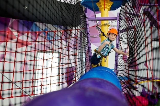 Rapaz alegre sobe nas cordas na tirolesa no centro de entretenimento. crianças se divertindo na área de escalada, crianças no fim de semana no parquinho, infância feliz