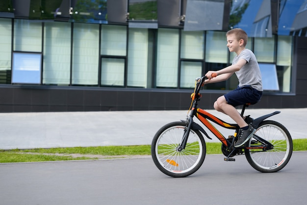 Rapaz anda de bicicleta sozinho na rua