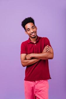 Rapaz animado e elegante posando com os braços cruzados. foto interna do entusiasmado modelo masculino em pé.