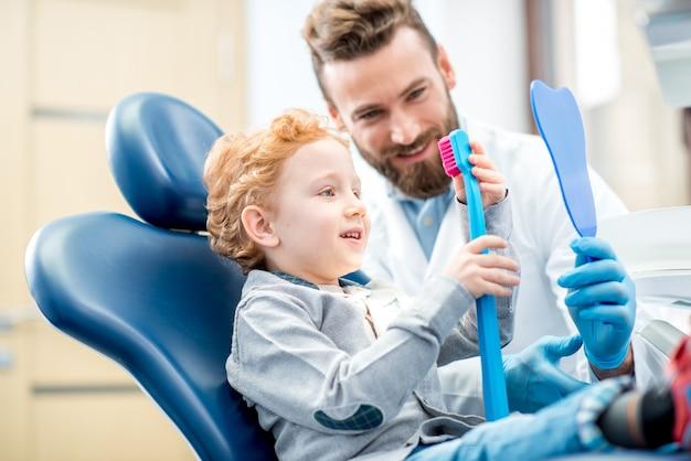 Rapaz animado sentado na cadeira segurando uma grande escova de dentes com o médico no consultório odontológico