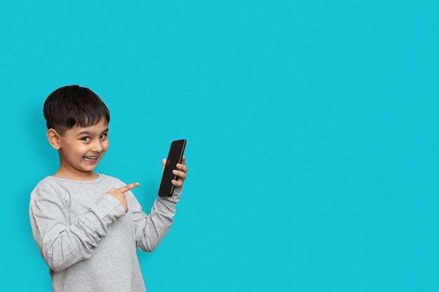 Rapaz animado, sorrindo e apontando para a tela do smartphone. em fundo azul simples com espaço de cópia