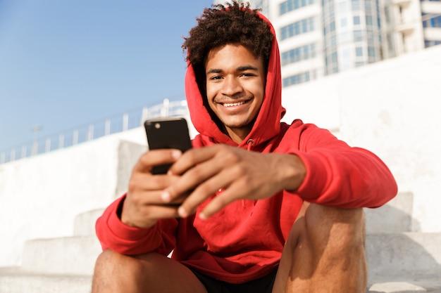 Rapaz ao ar livre na praia sentado em degraus sorrindo usando um telefone celular