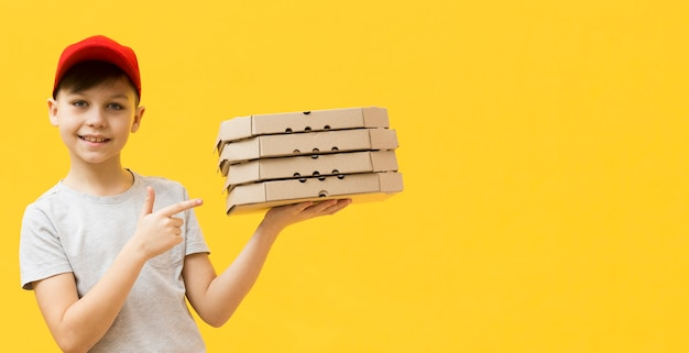 Rapaz, apontando para caixas de pizza
